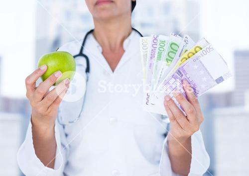 Doctor mid section with apple and money against blurry buildings