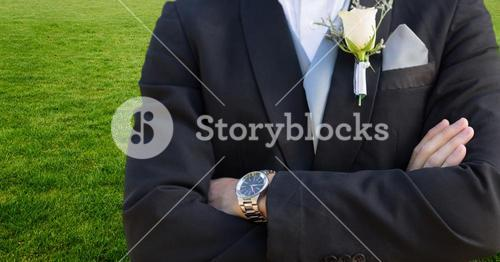 Groom mid section with arms folded against grass