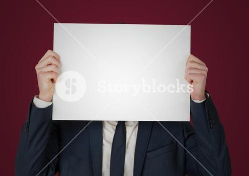 Business man with blank card over face against maroon background