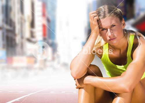 Sad disappointed athlete runner sitting down in city