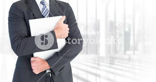Business man mid section holding laptop against blurry window
