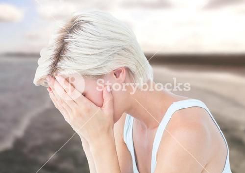 Sad woman with face in hands against sea landscape