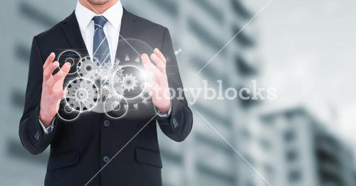 Business man with white cog graphics against blurry building