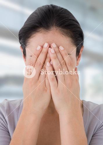 Sad woman grief hiding in hands against bright backgroun