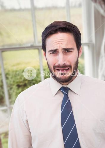 Businessman worried crying against countryside window