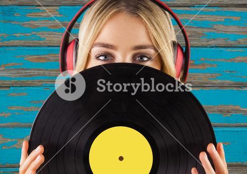 Woman with headphones and record against blue wood panel
