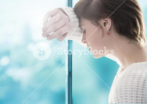 Sad woman grief leaning against a window