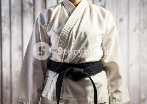 Woman in karate suit mid section against blurry wood panel