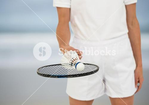 Badminton player mid section on blurry beach