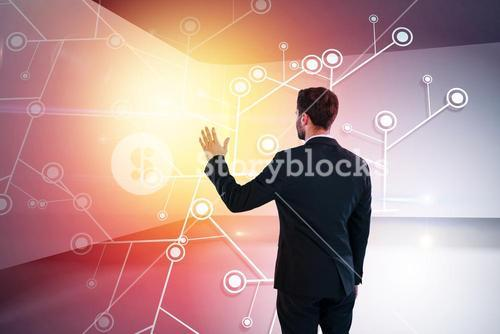 Composite image of rear view of businessman pretending to touch invisible screen