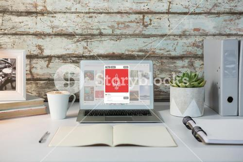 Composite image of overhead view of office desk with laptop and documents