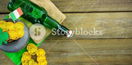St Patricks Day shamrock with flag and beer bottle by pot filled with chocolate gold coins