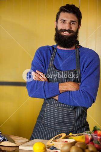 Portrait of male staff standing with hands crossed at organic section