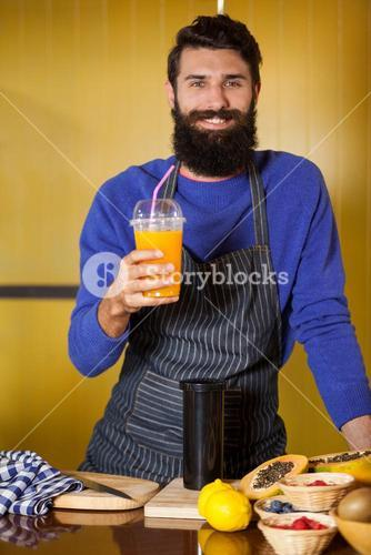 Portrait of male staff holding juice glass