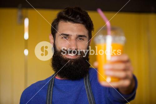 Male staff holding orange juice glass at organic section