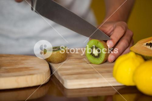 Mid-section of male staff cutting kiwifruit at organic section
