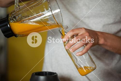 Male staff pouring juice in a bottle