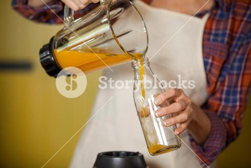 Female staff pouring juice in a bottle
