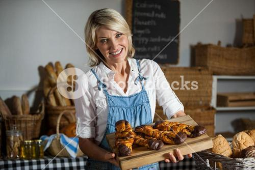 Female staff holding sweet foods in bakery section
