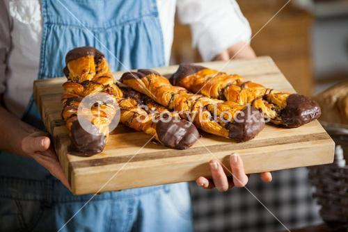 Mid-section of female staff holding sweet foods in bakery section