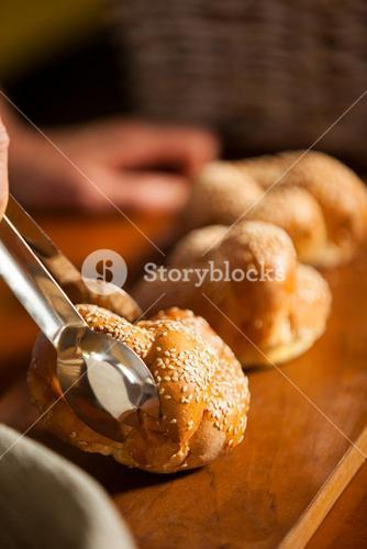 Hand of female staff holding sweet food with tongs