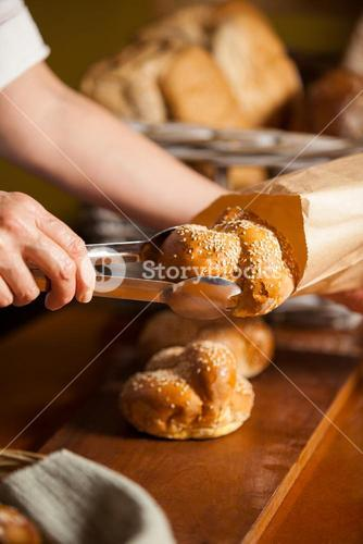 Hands of female staff packing sweet food in paper bag