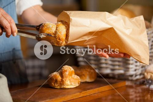 Mid-section of female staff packing sweet food in paper bag