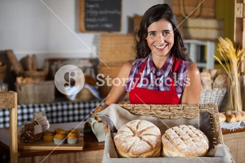 Smiling female staff holding wicker basket of breads at counter