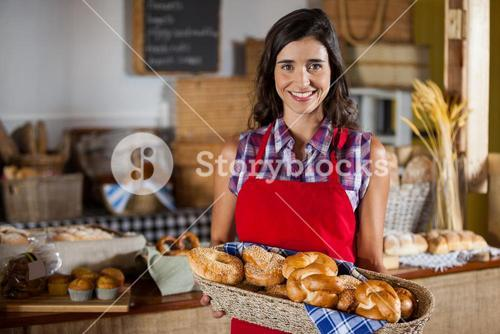 Smiling female staff holding wicker basket of various breads at counter