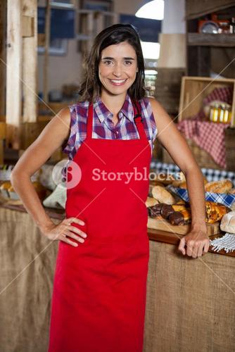 Portrait of smiling female staff standing with hands on hip at bakery shop