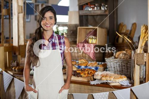 Portrait of smiling female staff standing with hands in pocket at bakery shop