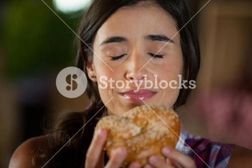 Smiling woman smelling a bread at counter