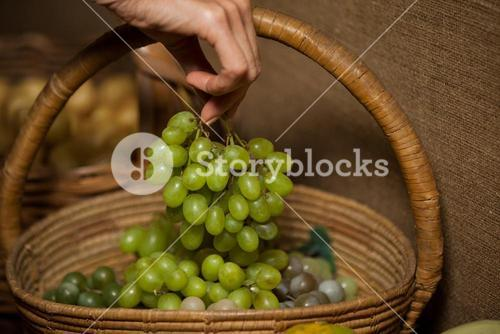 Hand of woman buying bunch of grapes