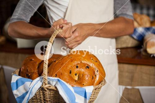 Mid-section of female staff holding wicker basket of breads at counter