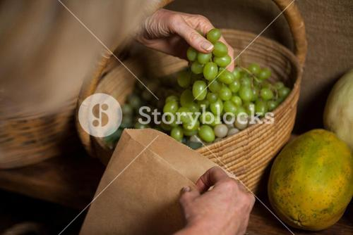 Staff packing grapes in paper bag