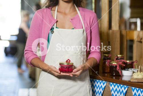 Mid-section of staff holding jar of maraschino cherry