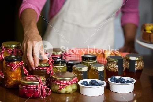 Mid-section of staff arranging jar at counter