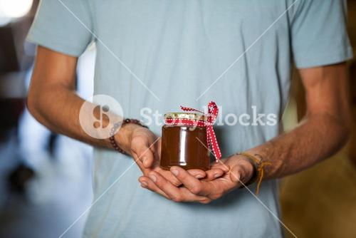 Mid-section of man holding a jar of jam