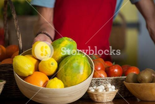 Staff holding a bowl of fruits at counter in market