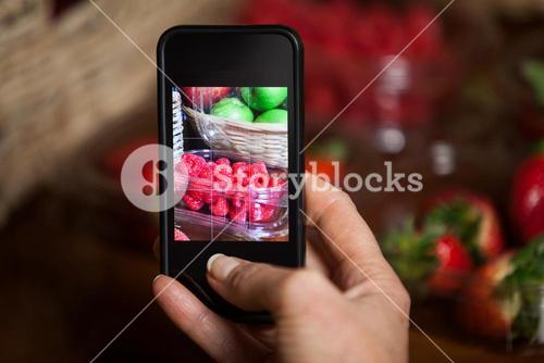 Hand of woman taking photo of fruits