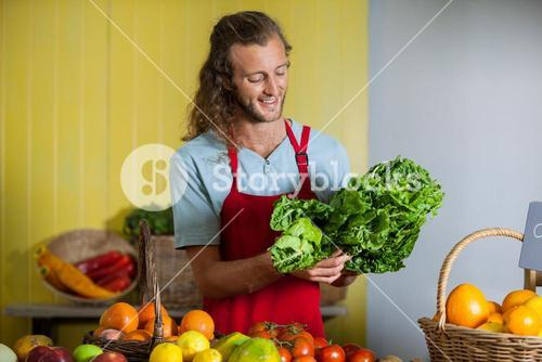 Smiling staff looking at leafy vegetables at counter