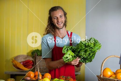 Smiling staff holding leafy vegetables at counter in market