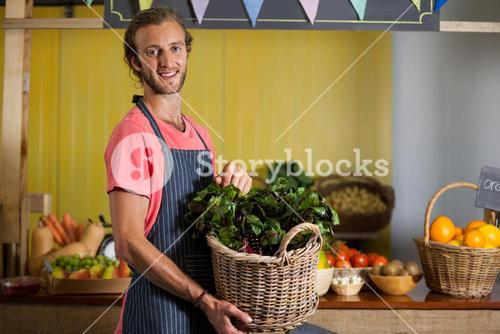 Smiling male staff holding leafy vegetables in basket at organic section