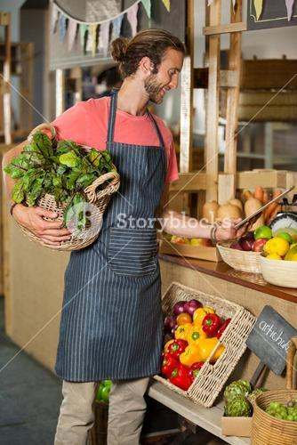 Male staff holding leafy vegetable and using digital tablet in organic section