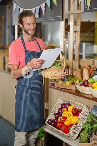 Male staff looking at clipboard in organic section