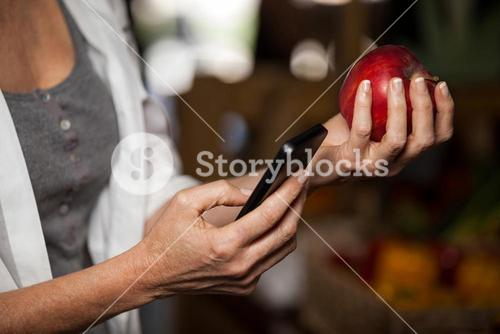 Mid section of female costumer holding apple while using mobile phone