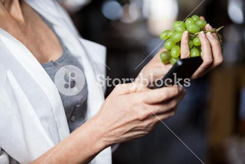 Mid section of female costumer holding grapes while using mobile phone