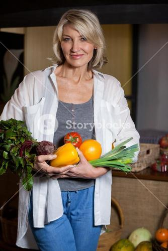 Portrait female costumer holding fresh vegetables and fruits in organic section