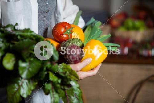 Mid section female costumer holding fresh vegetables and fruits in organic section