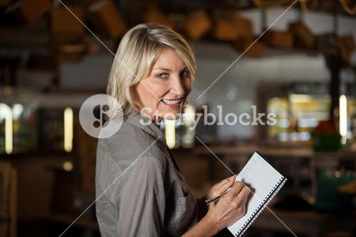 Portrait of female costumer maintain record in notepad
